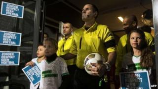 """Dutch referees stand next to children holding signs reading """"Without respect, no football"""" before a game in Almelo. Photo: 7 December 2012"""