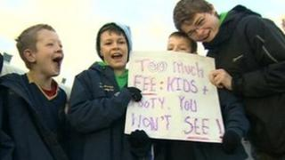 Children hold a placard protesting against council pitch fees