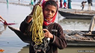 Rohit Kumar, 10, holding up his magnet rings tied to a yellow plastic rope