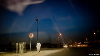 A man walking on the street at night in Misrata, Libya