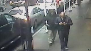 This still image made from a video provided by the New York City Police Department shows the gunman, left, behind Brandon Lincoln Woodard pulling the weapon from his jacket pocket a moment before the shooting, 10 December 2012