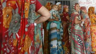 Women stand in a queue to cast their ballots outside a polling booth during the first phase of state elections at Sanand town in the western Indian state of Gujarat December 13, 2012