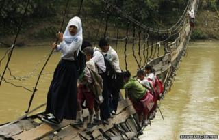 Students hold on to the side steel bars of a collapsed bridge as they cross a river to get to school at Sanghiang Tanjung village, Indonesia, 19 January 2012
