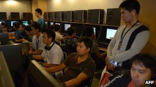 Customers sit at computer terminals in a Philippines internet cafe.