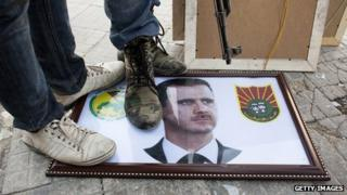 Syrian rebels stand on a picture of President Bashar al-Assad (20 August 2012)