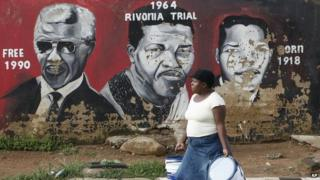 A woman walks past a mural depicting portraits of former South African President Nelson Mandela in Soweto, South Africa, Tuesday 11 December 2012
