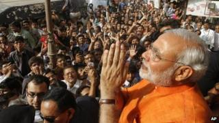 Narendra Modi greets his supporters after casting his vote in the second phase of Gujarat assembly elections in Ahmedabad on 17 Dec 2012