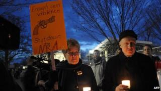 Gun control supporters take part in a candlelight vigil at Lafayette Square across from the White House on 15 December 2012, Washington