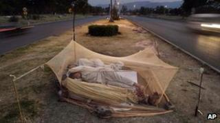 Labourers sleep under a mosquito net in the middle of a road in Islamabad, Pakistan, June 2012