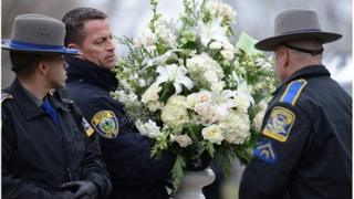 Police officers help with flowers at the funeral of Noah Pozner, aged six, in Fairfield, Connecticut, 17 December 2012