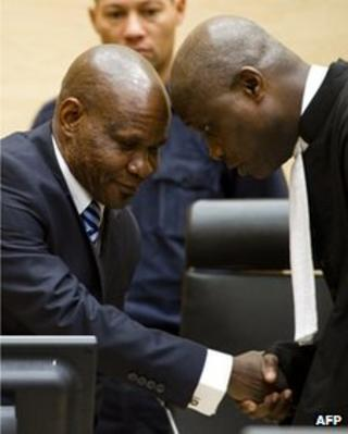 Mathieu Ngudjolo Chui (L) shakes hands with one of his lawyers at the ICC in The Hague on 18 December