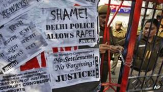 Indian police officers lock the gate of the police station during a protest condemning the gang rape of a 23-year-old student on a city bus late Sunday in New Delhi, India, Tuesday, Dec. 18, 2012. T