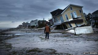 A man surveys the wreck of his house in Rockaway, New York, after the passage of Superstorm Sandy