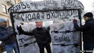 Activist wearing a mask of Ukrainian President Viktor Yanukovych protests against customs union with a symbolic gate