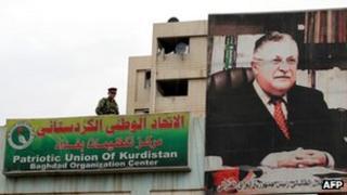 An Iraqi soldier stands guard next to billboard of Jalal Talabani in Baghdad