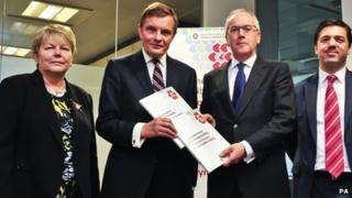 Paul Silk (second right), hands Welsh Secretary David Jones (second left), the Silk Commission report watched by with Baroness Jenny Randerson Wales Office Minister (left) and Stephen Crabb MP Wales Office Minister (right), at The Wales Office, Cardiff.