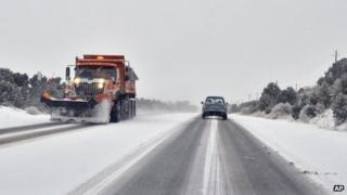 Drivers make their way cautiously in a snow storm along The Old Las Vegas Highway in Santa Fe 17 December 2012