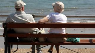 Elderly couple sitting on bench on sea front