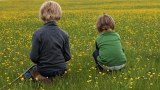 Two children in field - rear view