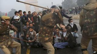 Protesters shield themselves as Indian police prepare to beat them with sticks (23 December 2012)
