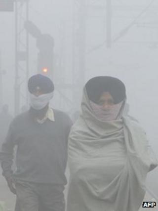 Indian passengers wait for their trains at a fog-covered railway station in Amritsar on December 24, 2012.