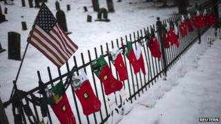 A US flag hangs over stockings left as a memorial for victims of the Sandy Hook Elementary School shooting, 27 December 2012