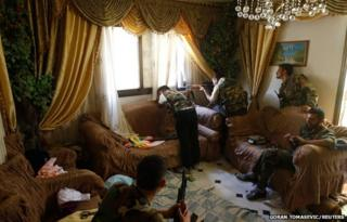 A Free Syrian Army fighter fires his sniper rifle from a house in Aleppo, Syria