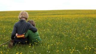 Two young brothers sit beside each other in a field of buttercups