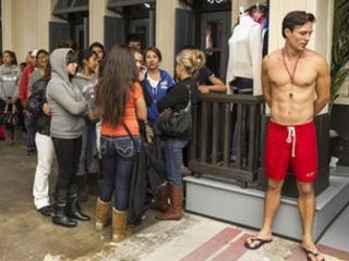 Model in swimming shorts at shop entrance