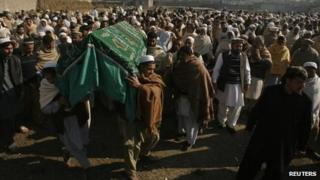 People carry the coffin of an aid worker who was killed by unidentified gunmen, during her funeral in Swabi January 2, 2013.