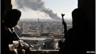 Free Syrian Army fighters watch smoke rising from buildings from their position during a fight with forces loyal to Syrian President Bashar al Assad at the front line in Aleppo December 26