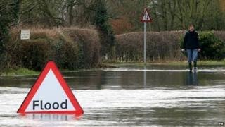 A man walks down a flooded road in Oxfordshire