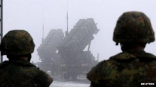 German soldiers look at Patriot missile batteries in Warbelow, northern Germany, on 18/12/12