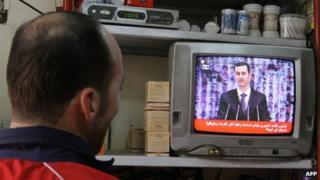 A man watches a TV showing Syrian President Bashar al-Assad making a public address in Damascus