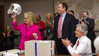 Hillary Clinton holds a football helmet with the seal of the State Department 7 January 2013
