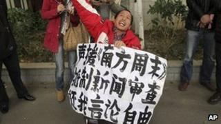 "A man holds a banner saying ""Support Southern Weekly, boycott news censorship and return my freedom of speech"" outside the newspaper""s headquarters in Guangzhou on 8 January 2013"