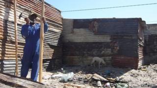 A man rebuilding a shack in Khayelitsha
