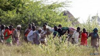 Residents carry the body of a man killed when their village was attacked in Kenya's Tana Delta region, 9 January 2013