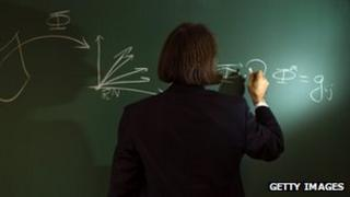 Mathematician writes out formula on a blackboard
