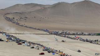 Hundreds of cars line the desert sands watching the competitors in the Dakar rally