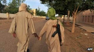 Two young fighters of the Islamist group Movement for Oneness and Jihad in West Africa (MUJAO) walk in the streets of Gao on July 17