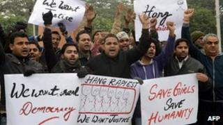 Protesting men with placards demanding rapists be hanged