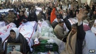 Shia sit between the coffins of bombing victims in Quetta. Photo: 12 January 2013