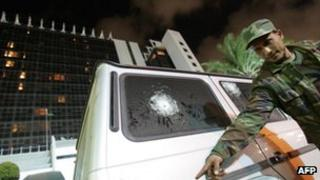 A Libyan security officer points to the damage of the bullet-proof vehicle in which Italy's consul to Benghazi was riding