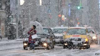 Woman walks through the snow in Ginza shopping district of Tokyo, Japan (14 Jan 2013)