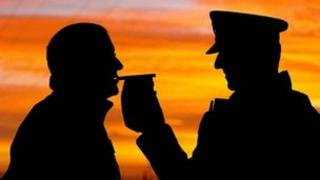 Silhouetted motorist gives a breath test to a police officer