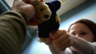 A child reaches for a soft toy