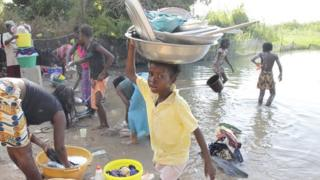 People washing up and bathing in the river near Lampsar, Senegal