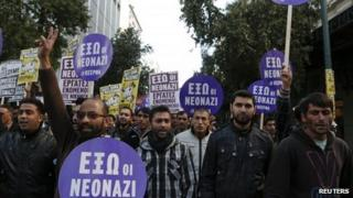"Immigrants hold banners reading ""Neonazis Out"" during an anti-racism rally in Athens, 19 January 2013"