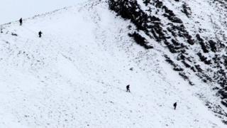 Climbers make their way down the mountains near Glencoe